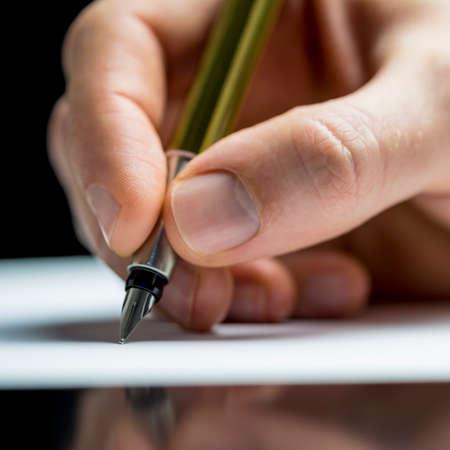 hombre escribiendo: Primer plano de la mano de un hombre que escribe una carta o notas con una pluma en una hoja de papel o la firma de un documento o contrato