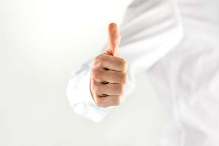 Motivated man giving a thumbs up sign showing his approval or success, high key image with copyspace and focus to his hand photo