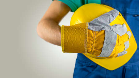 Workman wearing a protective glove holding a yellow hardhat or safety helmet conceptual of a builder, construction worker, tradesman or manual labourer