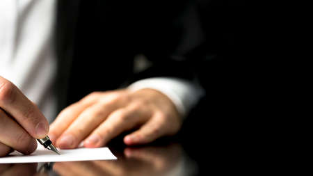 businessman signing documents: Businessman writing correspondence or signing a document using a fountain pen