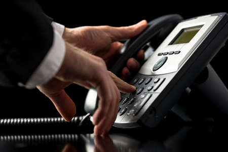 servicios publicos: Bajo el ángulo de vista de cerca de las manos de un hombre de negocios con un traje de marca hacia fuera en una llamada telefónica usando un instrumento de acceso telefónico de línea fija de escritorio mientras presiona los números en el teclado