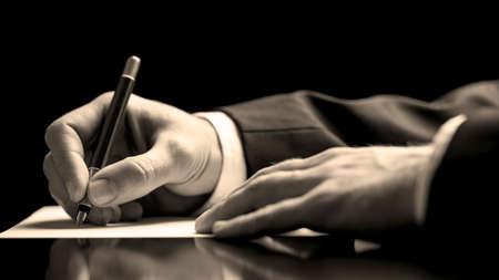 Close-up lage hoek perspectief van een zakenman in een pak ondertekening van een document met een vulpen als hij sluit een zakelijke deal of rondt een contract of overeenkomst