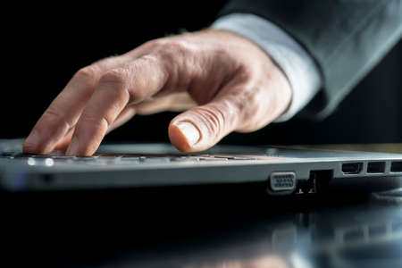 inputting: Low angle view of the hand of a businessman typing on a laptop computer keyboard inputting data or surfing the internet