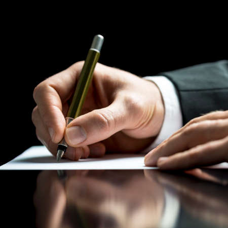businessman signing documents: Businessman writing on a sheet of white paper with a fountain pen as he signs an agreement or contract, writes correspondence, takes notes or completes a questionnaire, closeup low angle view