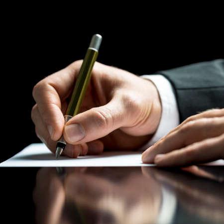 autoridad: Empresario escribiendo en una hoja de papel blanco con una pluma como él firma un acuerdo o contrato, escribe la correspondencia, toma notas o completa un cuestionario, primer ángulo de visión baja Foto de archivo