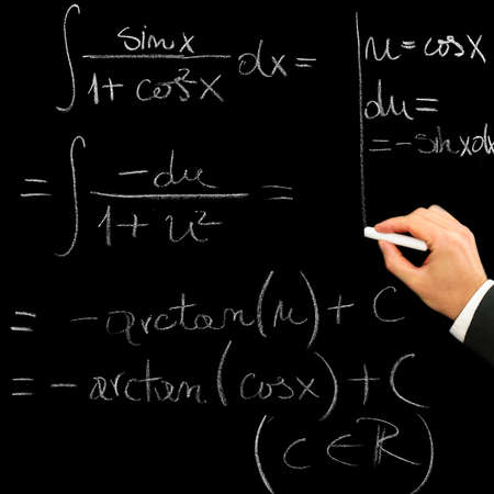 Close-up of a hand writing with chalk a mathematical exercise on the blackboard photo