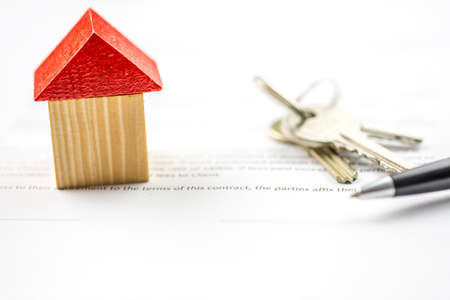 selling house: Keys and a pen lying on paperwork alongside a model of a house conceptual of ownership, purchase, selling or insurance and the signing of the contract Stock Photo