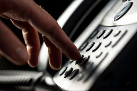 dialing: Closeup view of the hand of a man making a telephone call on a desktop instrument pressing the numbers on the keypad