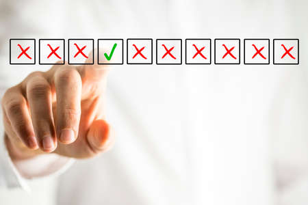 Man selecting the only green ticked check box from amongst a line of multiple boxes with red crosses on a virtual interface or screen in a conceptual image with copyspace