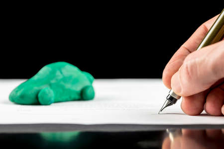 Conceptual image of the hand of a man signing a contract for the lease or purchase a green eco-friendly fuel efficient, electric or hybrid car with reduced carbon emissions photo