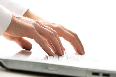 shirtsleeves: Closeup view of the hands of a man typing on a laptop computer inputting data and information for an online workflow or surfing the internet