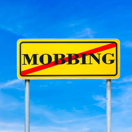 forbidding: Conceptual image of a bright yellow traffic sign showing Mobbing forbidden with the word - Mobbing - crossed through against a clear blue sky forbidding riotous crowds