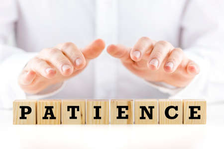 patience: Conceptual image with the word Patience on wooden blocks or cubes protected by the hands of a man sheltering them from above
