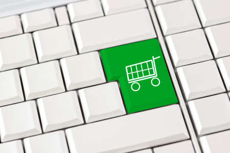 e store: Green shopping trolley icon on a computer keyboard conceptual of e-commerce and online shopping over the internet