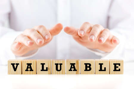Conceptual image with the word - Valuable- on a row of natural wooden cubes or blocks with a man holding his hands cupped protectively over the top shielding them
