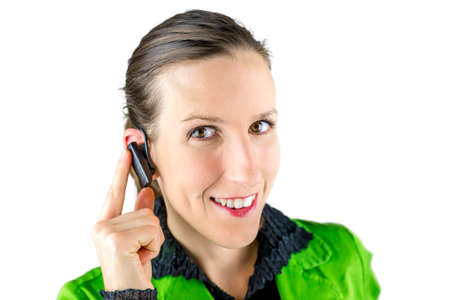 call center agent: Close-up portrait of a young Caucasian woman smiling while touching the small wireless hands free device placed at her right ear