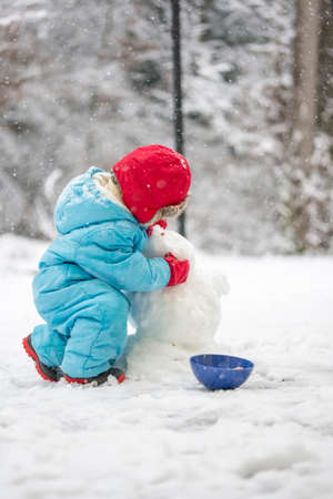 warmly: Young child building a snowman wrapped up warmly against the cold in a blue jumpsuit bending down in the cold white winter snow shaping the head, view from behind Stock Photo