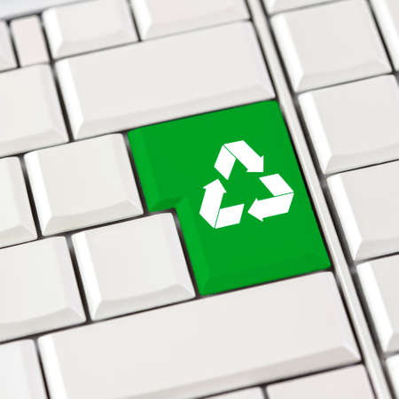 international recycle symbol: Green recycle icon on a computer keyboard with blank white keys conceptual of recycling materials to save the planet.