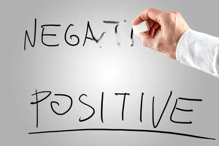 pessimistic: Man erasing Negative over Positive on a white screen in a conceptual image of opposing attitudes, attributes and qualities.