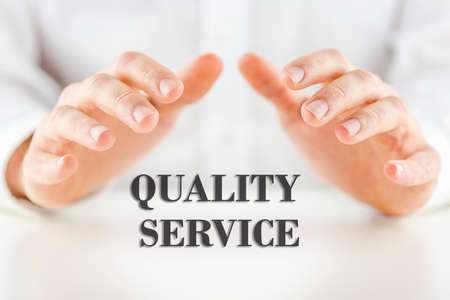 depicting: Conceptual image depicting customer satisfaction and quality reliable service and guaranteed support with a mans hand cupped protectively over the text - Quality Service. Stock Photo