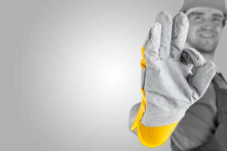 ハイライトと copyspace と灰色の背景に彼の手にフォーカスを持つ彼の手袋をはめた手で完璧なジェスチャーを作る職人。