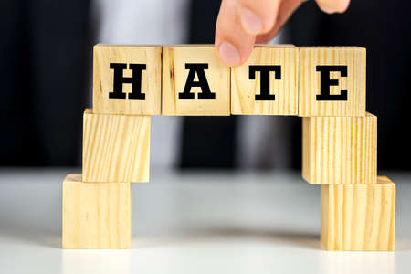 animosity: A person building a bridge of wooden cubes with word hate written on them.