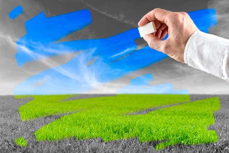 Konzeptionelle Bild eines Mannes, das Löschen Verschmutzung, als er über einen Graustufen-Landschaft, die grünen Wiesen und blauem Himmel, darunter findet sich reibt.