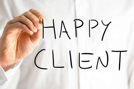 happy client: Man writing Happy Client on a virtual screen conceptual of feedback, support and quality service and products.