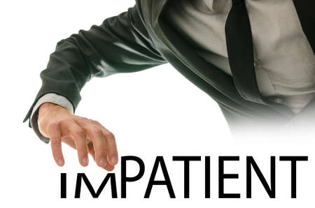 impatience: Businessman stretching his hand over the word Impatient