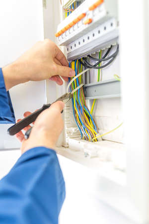 Electrician checking the wiring in a fuse box providing the electrical supply to a domestic residence either during installation as a new build or when called in to do maintenance and repairs.