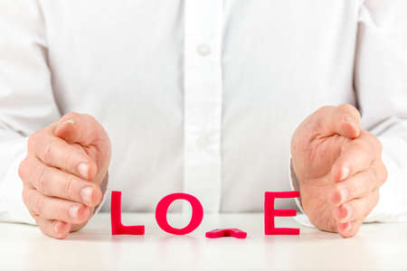 Conceptual image of a man trying to nurture a broken relationship with his hands held protectively around the word love in red letters with the V lying face down on the table. Stock Photo