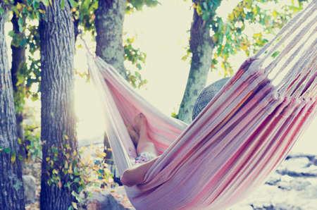 뜨거운 여름 날에 나무 그늘에서 해먹에서 휴식 사람은 뒤에서 볼 수 있습니다. 복고풍 필터 효과.