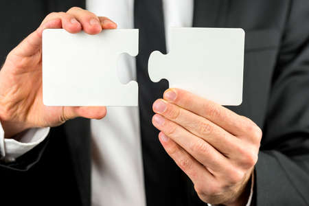 Closeup view of a professional businessman in a suit holding two pieces of a blank puzzle in his hand ready to fit them together in a concept of problems, planning, cooperation and solutions. photo