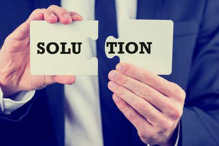 Geschäftsmann mit der Lösung eines Geschäftsproblems, die zwei Stücke eines Puzzles mit den Buchstaben - Lösungen - und - tion - bereit, um sie zusammen passen, um die Antwort zu finden. Mit Retro-Filter-Effekt.