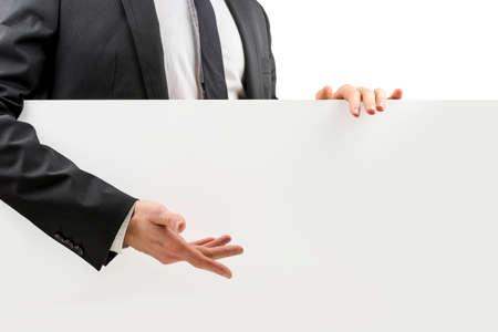 endorsing: Businessman in a suit gesturing to a blank white board with his hand that he is standing behind and holding with copyspace for your advertising or text, closeup torso view.
