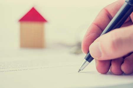 equidad: Imagen de estilo retro de un hombre que firma una escritura de compraventa, documento de la hipoteca o contrato de seguro en una casa con una vista de cerca de la mano con un pequeño modelo de madera de una casa.