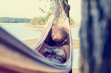 dream lake: Woman wearing a dress with floral pattern and covering her face with a straw hat while relaxing in a hammock outdoors, in a warm day of summer, next to a sea and a green area. With retro filter effect.