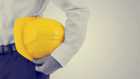 그의 팔, 복고 효과 노란색 hardhat 들고 사업가의 뷰를 닫습니다 copyspace와 머 금고 봐.