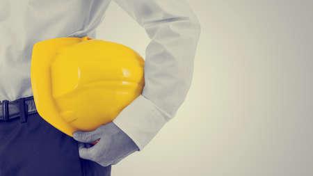 seguridad laboral: Cierre de vista de un hombre de negocios que lleva un casco amarillo bajo el brazo, efecto retro desvaneció mirar con copyspace. Foto de archivo