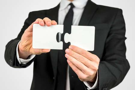 사업가 문제, 성장과 발전을 해결의 개념 그의 손에 두 개의 빈 흰색 퍼즐 조각을 들고.