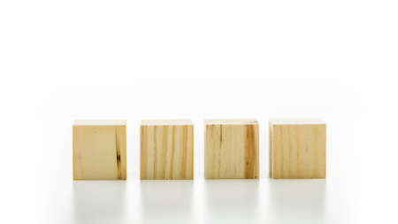 Four blank wooden cubes or building blocks lined up in a row on a reflective white surface with copyspace for your text, letters or numbers.