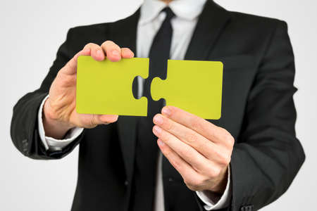 ability: Businessman in a suit holding two pieces of a yellow puzzle conceptual of problem solving, planning, creativity, development and challenge, close up view of his hands. Stock Photo