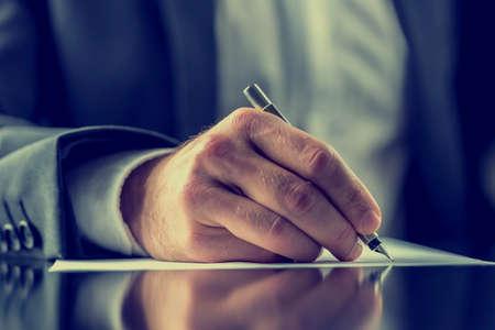 hombre escribiendo: El hombre que firma un documento o escribir correspondencia con una vista de primer plano de la mano con la pluma y la hoja de papel de carta en un escritorio. Con efecto retro filtro.