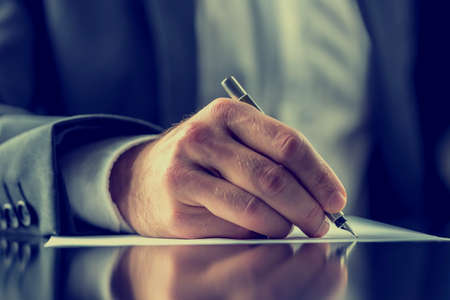 close up: Man signing a document or writing correspondence with a close up view of his hand with the pen and sheet of notepaper on a desk top. With retro filter effect.