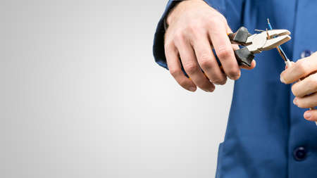 installation: Workman or electrician repairing an electrical cable with a pair of pliers to restore supply to the house, close up view of his hands in blue overalls on grey with copyspace Stock Photo