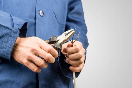electricista: Trabajador que repara un cable el�ctrico con un par de alicates. Sobre fondo gris con copyspace. Foto de archivo