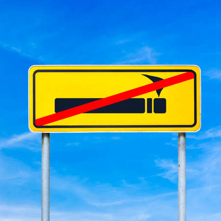 anti tobacco: Smoking forbidden or prohibited on a yellow traffic sign crossed through in red against a sunny blue summer sky, conceptual image. Stock Photo