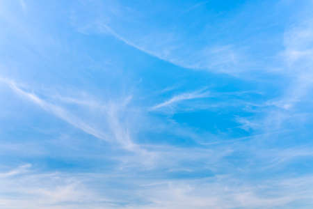 cirrus: Hazy blue summer sky background with wisps of fine cirrus clouds in an empty expanse of cerulean blue for a fresh tranquil nature abstract. Stock Photo