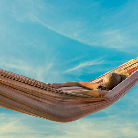 Woman relaxing in a hammock against a hazy blue sky with her straw sunhat shielding her face against the summer sun, square format. Stock Photo