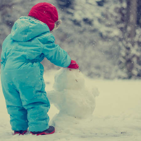 padded: Cute young toddler in a warm winter outfit standing in a cold wintry garden building a snow man from the fresh pristine white snow. With retro filter effect.